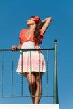 La muchacha hermosa en el balcón con el vestido de la moda y el pelo florecen imagenes de archivo