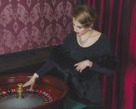 La muchacha hermosa en el casino hace girar la rueda de ruleta Imágenes de archivo libres de regalías