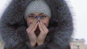 La muchacha hermosa en el parque del invierno calienta las manos frías metrajes
