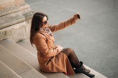 La muchacha hermosa en gafas de sol hace la foto en smartphone Selfie foto de archivo libre de regalías