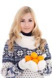 La muchacha hermosa en invierno viste con los mandarines aislados en pizca Foto de archivo libre de regalías