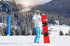 La muchacha hermosa en la chaqueta blanca, esquí azul jadea y googlea en su cabeza que se coloca con la snowboard en las montañas Fotografía de archivo libre de regalías