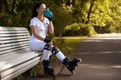 La muchacha hermosa en pcteres de ruedas en parque se sienta en banco y bebe el agua Imágenes de archivo libres de regalías