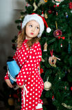 La muchacha hermosa en pijamas con el patín azul está esperando la Navidad y el Año Nuevo Foto de archivo