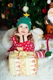 La muchacha hermosa en pijamas con la caja de regalo está esperando la Navidad y el Año Nuevo Foto de archivo libre de regalías