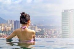 La muchacha hermosa en la piscina en el tejado del edificio admira las vistas de la ciudad imagen de archivo