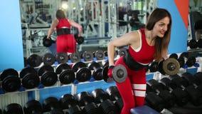 La muchacha hermosa en traje rojo hace la pesa de gimnasia de elevación del ejercicio, que se sostiene en manos almacen de metraje de vídeo
