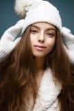 La muchacha hermosa en un blanco hizo punto el sombrero con el pompom de la piel Modelo con maquillaje desnudo apacible Imagen ac Fotos de archivo