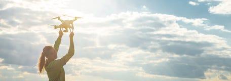 La muchacha hermosa en un campo lanza el abejón en el cielo fotos de archivo