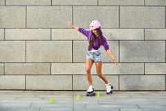 La muchacha hermosa en un casco aprende montar en los pcteres de ruedas que llevan a cabo la balanza Imagen de archivo libre de regalías