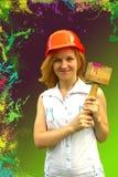 La muchacha hermosa en un casco con el martillo de la construcción en un verde y el fondo de Borgoña con salpica de la pintura Fotos de archivo