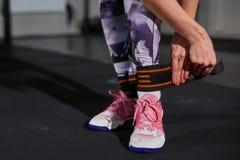 La muchacha hermosa en un gimnasio en un fondo de un muro de cemento sujeta una pierna en un vendaje elástico Ajuste de la cruz Imagenes de archivo