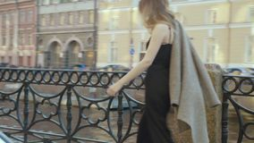 La muchacha hermosa en un mono de moda del cóctel va a lo largo de un terraplén de la ciudad en el slo-MES metrajes