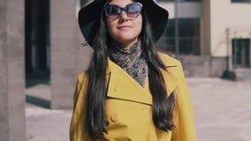 La muchacha hermosa en un sombrero amarillo y vidrios del impermeable va con equipaje y sonrisas almacen de metraje de vídeo