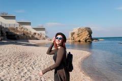 La muchacha hermosa en un sombrero vestido y vidrios va a lo largo de la playa y es feliz Imagenes de archivo