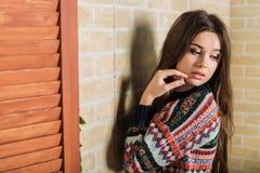 La muchacha hermosa en un suéter hecho punto multicolor se coloca cerca de la pared de ladrillo Cerca de la ventana Imagenes de archivo