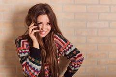La muchacha hermosa en un suéter hecho punto multicolor se coloca cerca de la pared de ladrillo Cerca de la ventana Fotos de archivo libres de regalías