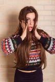 La muchacha hermosa en un suéter hecho punto multicolor se coloca cerca de la pared de ladrillo Cerca de la ventana Imagen de archivo