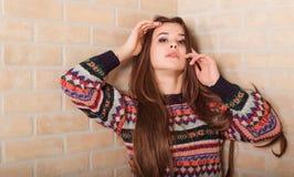 La muchacha hermosa en un suéter hecho punto multicolor se coloca cerca de la pared de ladrillo Cerca de la ventana Fotografía de archivo libre de regalías