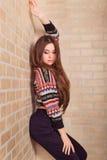 La muchacha hermosa en un suéter hecho punto multicolor se coloca cerca de la pared de ladrillo Cerca de la ventana Foto de archivo