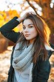 La muchacha hermosa en un suéter hecho punto y la chaqueta en el otoño equiparan Imagenes de archivo