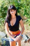 La muchacha hermosa en un top y un dril de algodón negros pone en cortocircuito la situación en un rocho Imagen de archivo