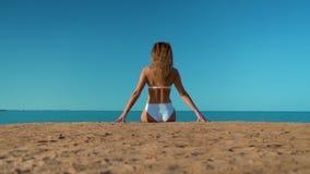 La muchacha hermosa en un traje de ba?o blanco que se sienta en el fondo del mar almacen de video