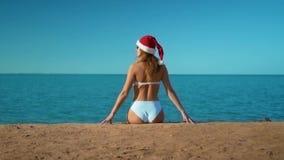 La muchacha hermosa en un traje de ba?o blanco y en el sombrero de Pap? Noel que se sienta en el fondo del mar almacen de metraje de vídeo