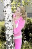 La muchacha hermosa en un traje rosado ocultó detrás de un abedul Foto de archivo libre de regalías