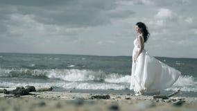 La muchacha hermosa en un vestido blanco se coloca en la costa La mujer está sosteniendo un vestido que agite en la cámara lenta  metrajes