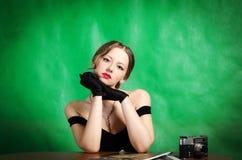 La muchacha hermosa en un vestido de noche se sienta en una tabla con revistas y una cámara de la película del telémetro imagen de archivo libre de regalías
