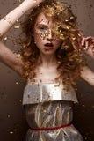La muchacha hermosa en un vestido de noche y un oro se encrespa Modele en imagen del ` s del Año Nuevo con brillo y malla Foto de archivo