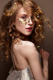 La muchacha hermosa en un vestido de noche y un oro se encrespa Modele en imagen del ` s del Año Nuevo con brillo y malla Fotos de archivo libres de regalías