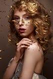 La muchacha hermosa en un vestido de noche y un oro se encrespa Modele en imagen del ` s del Año Nuevo con brillo y malla Imagenes de archivo