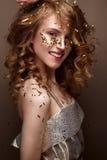 La muchacha hermosa en un vestido de noche y un oro se encrespa Modele en imagen del ` s del Año Nuevo con brillo y malla Imágenes de archivo libres de regalías