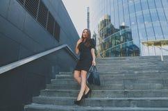 La muchacha hermosa en un vestido negro camina abajo de las escaleras que sostienen un bolso Imagen de archivo libre de regalías