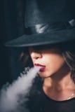 La muchacha hermosa en un vestido negro fuma la cachimba en cadenas del fondo imagen de archivo