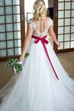 La muchacha hermosa en un vestido que se casa se coloca en el medio del cuarto con el suyo de nuevo a la cámara foto de archivo