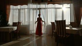 La muchacha hermosa en un vestido rojo va a una ventana en el cuarto almacen de video