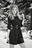La muchacha hermosa en una alineada negra contra nieve Imagen de archivo