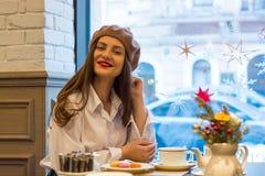 La muchacha hermosa en una boina se sienta en una tabla en un café con una taza de té, macarrones imágenes de archivo libres de regalías