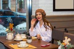 La muchacha hermosa en una boina se sienta en una tabla en un café con una taza de té, macarrones imagenes de archivo
