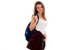 La muchacha hermosa en una camiseta blanca y una cartera en el hombro se levanta recta y de mirada de la cámara aislada encendido Fotos de archivo libres de regalías