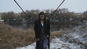 La muchacha hermosa en una capa del traje va por el río metrajes