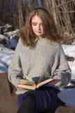 La muchacha hermosa en una chaqueta gris, una falda púrpura se sienta en una manta en un bosque del invierno y lee un libro Foto de archivo libre de regalías