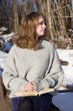 La muchacha hermosa en una chaqueta gris, una falda púrpura se sienta en una manta en un bosque del invierno y lee un libro Imágenes de archivo libres de regalías