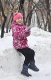 La muchacha hermosa en una chaqueta juega en el parque en el invierno Fotos de archivo libres de regalías