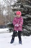 La muchacha hermosa en una chaqueta juega en el parque en el invierno Imagen de archivo