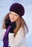 La muchacha hermosa en una púrpura hizo punto el sombrero y la bufanda del invierno Foto de archivo