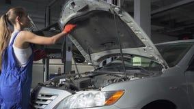 La muchacha hermosa en uniforme cierra la capilla de la situación del coche delante del vehículo en la gasolinera Coche almacen de video